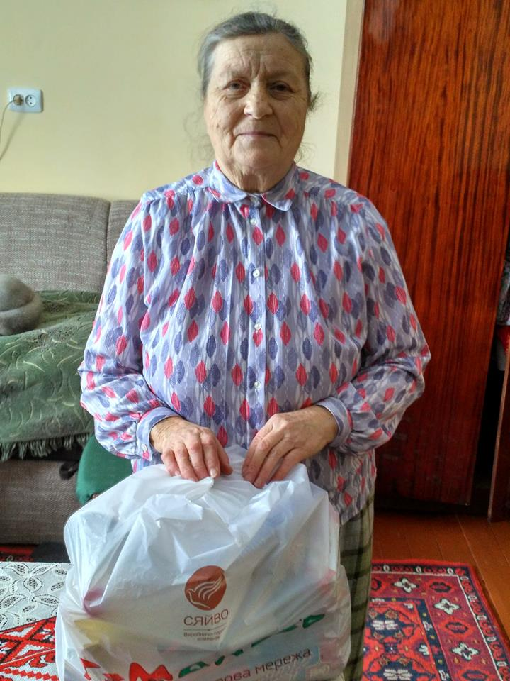 Elderly Ukrainian woman with food package delivered by Vasyl and youth from Boryslav Baptist Church.