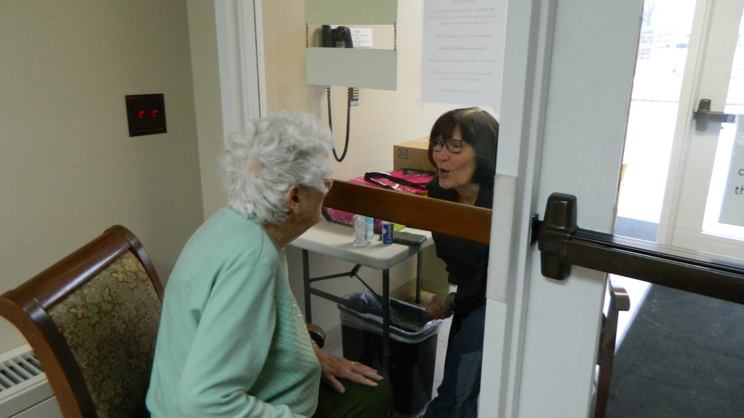 Elderly woman visits with woman through glass door